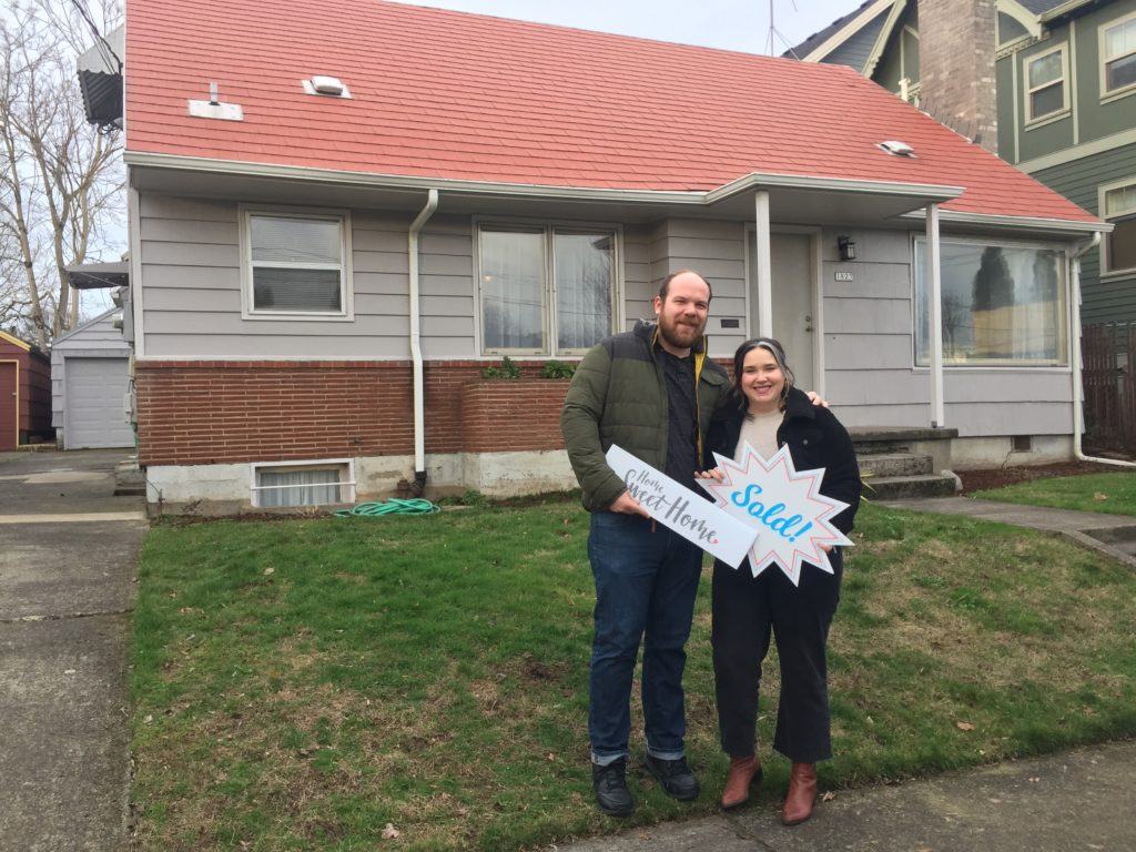 First time buyers in front of their first home in Sellwood.